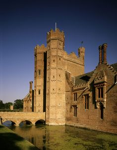 The imposing Gatehouse of Oxburgh Hall rising from the moat and showing the bridge across the moat
