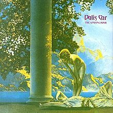 """A predominately green, yellow, and blue saturated Ancient Greek-style image of a girl lying down smiling and another girl standing above her, naked, looking down at her. Next to them is a column. The leaves of a tree are visible directly behind the column. In the background is a large mountain, separated by the sea. """"Dalis Car"""", with """"The Waking Hour"""" below it in smaller text, are imprinted in fantasy-style purple text in the upper-right corner."""