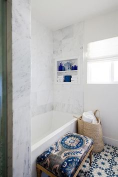 Gorgeous bathroom features a drop-in tub lined with a white marble surround fitted with a niche ...