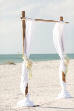 wedding arch on the beach--simple! Looks like bamboo, so hopefully cheap to construct as well