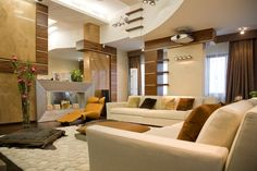 Modern living room with 2-story ceiling with earth tones throughout.