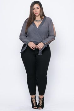 This plus size, stretch knit blouse features a v-neckline with a cross wrap style and ribbon accent, long sleeves with open slits and ribbon detailing at cuff,