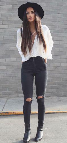 Musa do estilo: Sophia Miacova. Chapéu preto, camisa branca, calça skinny preta com rasgo no joelho, ankle boot preta