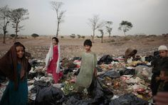 An Afghan refugee boy (center) looks on while he and others collect items of potential use from a pile of garbage, on the outskirts of Islamabad, Pakistan on June 6. (Nathalie Bardou/Associated Press)