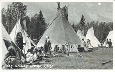 Prairie Postcards PC009756: Harmon Byron, Stoney Indian Camp ([before 1942])  Men and women in front of tipis near Banff watching something out of frame. (Seat of carriage or open-topped motorcar just visible between tipis on left?)