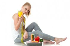 girl holding health food with tape measure and scale