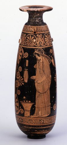 480BC-470BC  Attic   A hetaira in a long sleeved chiton, with apoptygma, to left, in the act of putting on her girdle; with an end of the girdle in each hand, she is about to tie it, holding up in her teeth the part of her apoptygma which is to fall over the girdle. She has long hair and a radiated fillet. At her feet is a calathos filled with wool, in which are three circular objects. On the left, an alabastron, as in (a); on the right, a lekythos hangs. ΚΑΛΕ (retr.), ΗΕΠΑΙΣ, ό παις καλή.
