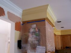 add crown molding to the ceiling above the cabinets and add some trim molding to the bottom of the soffit.