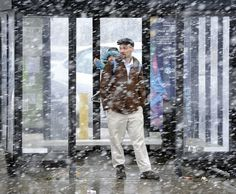 Another spring day in Spokane: Andrew Farris, and his daughter, Trinity Mace-Farris, 2 years old, take shelter from Monday's snow storm as they wait in an STA bus shelter. Photo by Dan Pelle.  #spokane #weather
