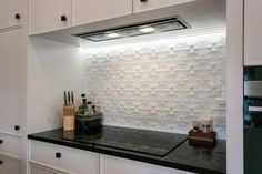Integrated range hood with hob and black stone bench top