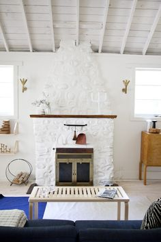 This fabulous cottage renovation  features natural pine floors and simple practical furniture. Check out the beautiful, large white fireplace in the center of the living room.