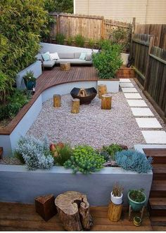 small but cozy outdoor living space. deck space with seating area, gravel space with fireplace and concrete planters