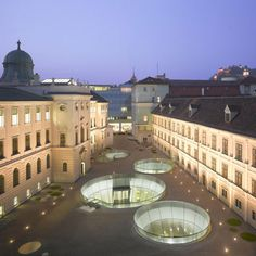 Cavernous holes in the courtyard of three museum buildings in Graz, Austria, lead underground into a new, shared entrance by Spanish architects Nieto Sobejano and local firm eep architekten.
