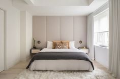 master bedroom with custom nightstands and an upholstered back wall: