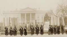 "Members of the National Women's Party (formed by Alice Paul) in front of the White House, 1917; sign reads: ""Mr. President, how long must wo..."