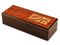 This stunning Wenge box features a scrolling marquetry design fitted precisely into a Madrone Burl top. The Tiger Maple and Bloodwood design is cut through with soaring piece of black Obeche. Inside, a single sliding tray keeps pieces organized and accessible. Mitered corner construction ensures durability while our single-piece creation method keeps continuity in grain and color throughout the box. Felt feet and the artist's signature engraved into the bottom afford a final touch of artistry. T Handmade Jewelry Box, Wooden Jewelry Boxes, Wood Box Design, Carpentry And Joinery, Diy Jewelry Rings, Jewellery, Woodworking Inspiration, Woodworking Projects, Marquetry
