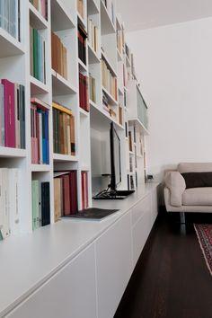 """Libreria con ripiani e montanti sfalsati. Cassettiera come base per supporto TV e pensile con funzione """"angolo bar""""."""