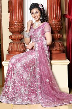 Ornate pink lehenga choli with heavy crystal beading, and a cropped top with sheer, netted short sleeves.
