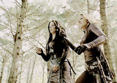 Celeste heard the snap of a bow and shoved Araelya to the ground, away from the soaring arrow. Glancing upwards, the blonde sorceress caught sight of a hooded figure jumping from tree to tree with a bow and arrows strapped to her back.