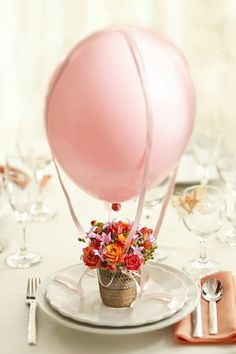 This adorable hot air balloon might look difficult to make, but it's really easy. If you don't have helium, then use a clear straw to keep the balloon upright.  Using two pieces of ribbon, tie them around the balloon as straps. You want them to criss cross over the top.  http://m.www.1800flowers.com/blog/julie/holiday-decorations/mothers-day/diy-mothers-day-craft-how-to-make-a-floral-hot-air-balloon-for-mom/?flws_rd=2