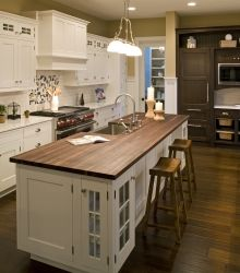 Butcher block island and white kitchen cabinets, like the range hood