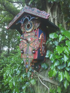 bird house in multi-colour with much fine wood carved details.