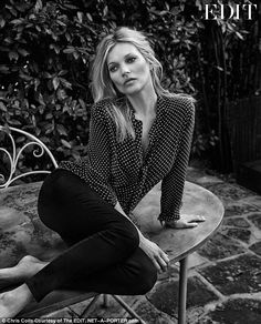 Signature style: A more romantic black-and-white shot sees the beautiful blonde recline on table, clad in a polka dot pussybow blouse and skinny jeans