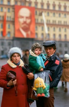 A family posing in front of a poster of communist revolutionary and first Premier of the Soviet Union Vladimir Lenin, Red Square, Moscow, Russia, USSR, 1987, photograph by Peter Turnley.