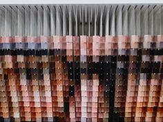"""Andrew Myers, artista californiano em Laguna Beach, suspendeu 1.200 cubos de acrílico pintados à mão em uma altura de 731 metros por meio de um fio de aço inoxidável para criar uma escultura notavelmente precisa que, quando vista de frente, forma a face pixelizada de um homem. Intitulada """"My Dealer is Not a Square"""" (ou """"Meu Revendedor Não é um Quadrado""""), o retrato original descreve Lawrence Cantor, negociante de arte de Myers em uma configuração abstrata e  realista ao mesmo tempo."""