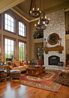 wonderful 2-story family room with stone fireplace and 3 stunning chandeliers