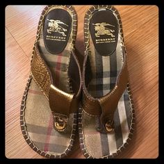 "Authentic Burberry Wedge Espadrilles Burberry Bronze metallic wedge espadrille sandals.  T-strap made of soft leather and the footbed contains the classic Burberry nova check print.  Rubber soles with raffia espadrille.  Does not come with box.  Very good used condition with little wear on the soles.  Burberry emblem on leather heel nearly fully intact!  Has ""Burberry"" engraved on the metal rings around the thong.  I have a running injury that no longer allows me to wear thong-styled shoes…"