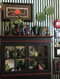 The green and white striped wallpaper makes a simple yet bold pallet for loved accessories!!!