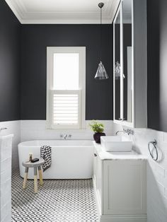 If you're not planning on tiling to the ceiling why not choose a statement colour like this bathroom where they have used a charcoal coloured paint for impact