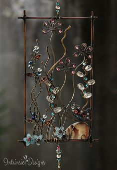 BUTTERFLY GARDEN SUNCATCHER FOR YOUR WINDOW A pretty Summer garden of unusual flowers with a Butterfly resting on a rock of Crazy Lace Agate. CONSISTING OF.... Garnet marquise briolettes Garnet micro faceted rounds Garnet teardrop briolettes Neon Blue Apatite Pink Tourmaline Clear Rock Crystal Crazy Lace Agate cabochon Blue, Clear, Pink Genuine Swarovski Crystal Blue Austrian Crystal The raw metals are a mix of Copper, Phosphor Bronze, Jewellers Bronze and Brass .. Oxidised and polished…