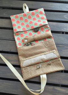 Unique travel jewelry roll that has 8 small pockets, one large slip pocket, one large zipper pocket and a ring and necklace holder with a snap for