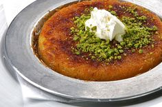 """KUNEFE -   the wirey shreds are called """"tel kadayıf"""". A semi-soft cheese such as Urfa peyniri (cheese of Urfa, or Hatay peyniri, cheese of Hatay), made of raw milk, is used in the filling.In making the künefe, the kadayıf is not rolled around the cheese; instead, cheese is put in between two layers of wiry kadayıf. It is cooked in small copper plates, and then served very hot in syrup with clotted cream (kaymak) and topped with pistachios or walnuts. In the Turkish cuisine, there is also…"""