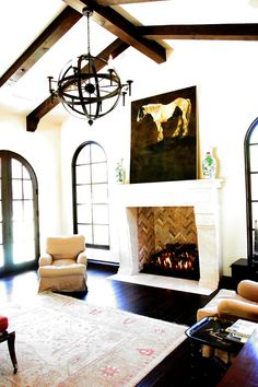 gorgeous chandelier and wood beam ceiling... And the chevron pattern in the fire place. Love!