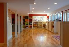 """Great play room!!  Build in storage. """"This is your chance to increase your opportunities for organization and storage,"""" says Hullinger. """"Don't leave this out of your plans."""" Built-in bookshelves across the wall of a basement can corral anything from toys to throw blankets to ski gear."""