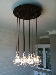Custom Industrial Chandelier with Modern Glass Pendants in polished nickel sockets hung from rayon cord attached to premium base. $550.00, via Etsy.