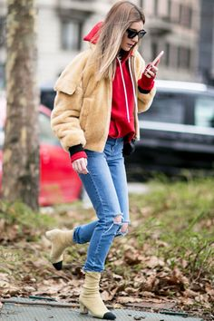 A faux fur bomber jacket is worn with a sweatshirt, distressed denim, and cap toe booties