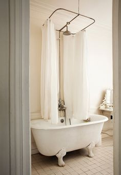 centered shower curtain rod for original claw foot tub in an apartment in paris