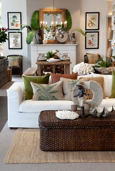 Brown rattan coffee table with hemp rug, white lounge and tropical cushions create a plantation style.