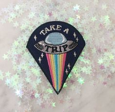 Take a trip with this far out UFO patch.  Rainbow light beams pop against the night sky & glisterning metallic silver stars.  Wildflower + Co. iron on patches.