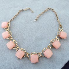Offering this very pretty, pink thermoset choker necklace from the 50s - 60s. This necklace is short, only 16 long. It has a goldtone base and is in