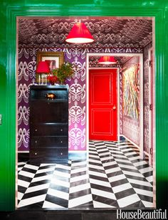Vivid colors and patterns — from Quadrille's Nomad fabric on the walls and ceiling to the silk shades of custom lamps by Blanche P. Field to an upholstered patent leather door — make a bold statement in the foyer.