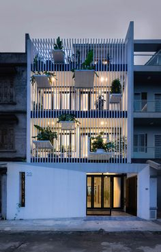Big shelves create places for displaying pot plants on the facade of this house that DANstudio has completed on the outskirts of the Vietnamese capital #greenbuilding