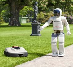 Honda's Asimo walking talking robot shows off the company's new lawn mower, Milmo, which is operated by robotics technology. (AP Photo/Honda Motor Co.)