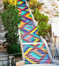 """Cansados da guerra na Síria, um grupo de jovens resolveu dar cor para a maior escadaria da cidade de Deir Atieh. O projeto foi um sucesso e o local recebeu o nome de """"Escada da Paz""""."""