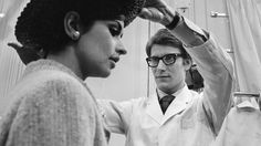 Yves Saint Laurent works with a model at his Paris fashion house in 1965. A new film follows the designer's rise in the fashion world.