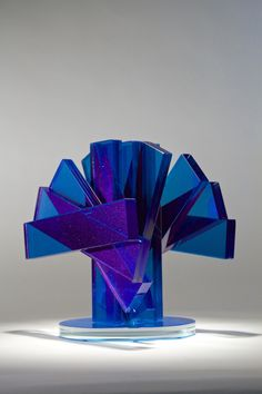 """Shifting Transmission #1. 2014, 11""""x8""""10"""". This piece was created by laminating clear bars of glass together with ultraviolet adhesive that had blue and sparkle, special effect pigment added. The bars were then ground and polished before laminating into a helical sculpture."""